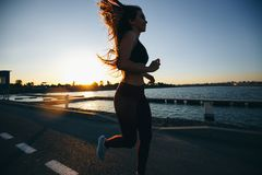 Gorgeous young girl with long brown hair dressed in sports clothes runs on the road along the reservoir on the sunset royalty free stock photos