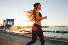 Gorgeous young girl with long brown hair dressed in sports clothes runs on the road along the reservoir on the sunset stock images