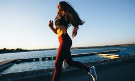 Gorgeous young girl with long brown hair dressed in sports clothes runs on the road along the reservoir on the sunset royalty free stock photography