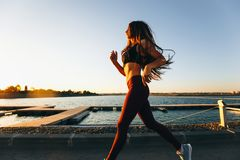 Gorgeous young girl with long brown hair dressed in sports clothes runs on the road along the reservoir on the sunset royalty free stock photo