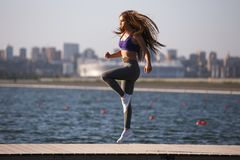 Gorgeous young girl with long brown hair in a sports top and tights jumps on the wooden pier stock images