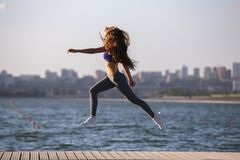Gorgeous young girl with long brown hair in a sports top and tights jumps on the wooden pier . royalty free stock photos