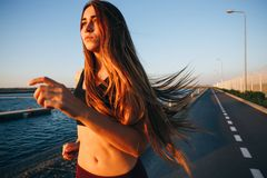Gorgeous young girl with long brown hair in a sports top and tights runs on the road along the reservoir on the sunset stock image