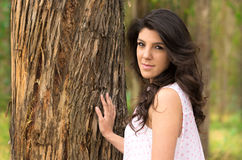 Gorgeous young girl posing besides a tree Stock Photo
