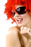 Gorgeous young girl in red feathers. With tongue ring exposed Royalty Free Stock Image