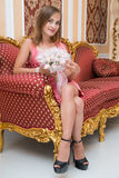 Gorgeous young girl sitting on luxurious sofa and holding flowers Stock Images