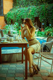 Gorgeous young girl in sunglasses and short dress drink coffee o Royalty Free Stock Photo