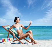 Gorgeous young girl with a suntan cream on the beach Stock Images