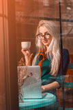 Gorgeous young happy blond business woman with a cup of tea in a Royalty Free Stock Photography