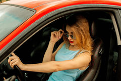 Gorgeous young lady in car. Gorgeous young lady with beautiful makeup in sunglasses driving a red car Royalty Free Stock Photography