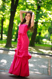 Gorgeous young lady in long dress in summer park Royalty Free Stock Image