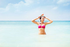 Gorgeous, young lady in pink swimwear with a snorkeling mask swimming in the sea Stock Image