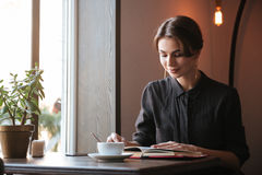 Gorgeous young lady sitting at the table reading book. Photo of gorgeous young lady sitting at the table reading book in cafe and looking aside while drinking Royalty Free Stock Images