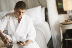 Gorgeous young man (gentleman) lying on a bed at the hotel. Stock Image