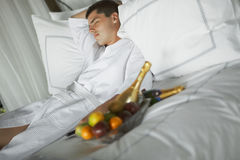 Gorgeous young man (gentleman) lying on a bed at the hotel. Royalty Free Stock Photos