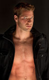 Gorgeous Young Man in Open Jacket. An image of an attractive, muscular guy with an intense, serious look, staring at the viewer Stock Photo