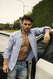 Gorgeous Young Man with Shirt Open on Naked Muscular Torso Getting Out his Car Royalty Free Stock Photography