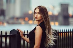 Gorgeous young model woman with perfect blonde hair looking at camera posing in the city wearing black evening dress.  Stock Image