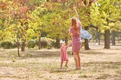 Cute girl playing with mom, flying a kite on the autumn park background. Happy family concept. Copy space. stock photography