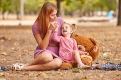 Happy mom and cute daughter playing with teddy bear on a park background. Plush toys concept. stock photos