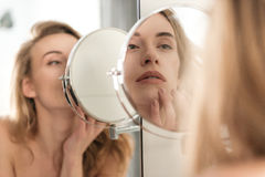 Gorgeous young naked woman looking at mirror. Image of gorgeous young naked woman standing in bathroom looking at mirror stock photo