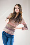 Gorgeous young poser. Portrait of fashionable young brunette girl in blue jeans and sweater Royalty Free Stock Photos