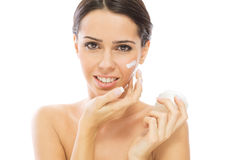 Gorgeous young woman applying face cream Stock Image