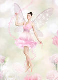 Gorgeous young woman as flower fairy. On flowery background royalty free stock photography