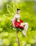 Gorgeous young woman as spring fairy. Sitting on red flower on green background royalty free stock photos