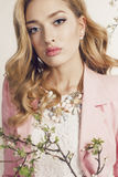 Gorgeous young woman with blond curly hair wears elegant suit and bijou Stock Photo