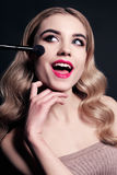Gorgeous young woman with blond hair, making make up Stock Photos