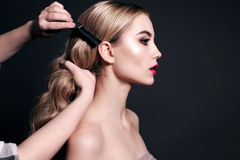 Gorgeous young woman with blond hair, making make up Royalty Free Stock Images