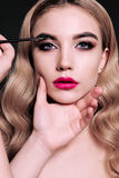 Gorgeous young woman with blond hair, making make up Stock Image