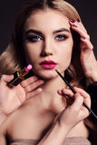 Gorgeous young woman with blond hair, making make up Royalty Free Stock Photos