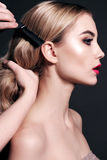 Gorgeous young woman with blond hair, making make up Royalty Free Stock Image