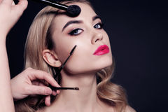 Gorgeous young woman with blond hair, making make up. Fashion studio portrait of gorgeous young woman with blond hair, making make up Stock Photo