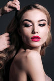 Gorgeous young woman with blond hair, making make up. Fashion studio portrait of gorgeous young woman with blond hair, making make up Royalty Free Stock Photo