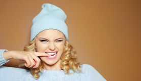 Gorgeous young woman with blond ringlets in a green knitted winter outfit Royalty Free Stock Photos