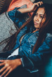 Gorgeous young woman in blue jeans chilling in a club. Portrait of a beautiful young woman in fashionable outfit Stock Photos