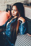Gorgeous young woman in blue jeans chilling in a club. Portrait of a beautiful young woman relaxing Stock Photography