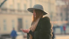 Gorgeous young woman in a bright sunlight uses her phone. While standing in the city center, gladly texts back, looks around. Urban buildings, passersby on the stock footage