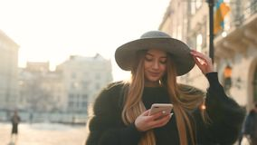 Gorgeous young woman in a bright sunlight uses her phone while standing in the city center. Dials text in the phone, looks around. Urban buildings, passersby stock footage
