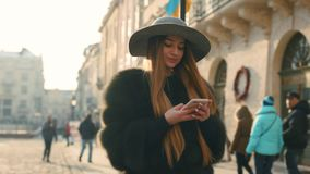 Gorgeous young woman in a bright sunlight uses her phone while standing in the city center stock footage