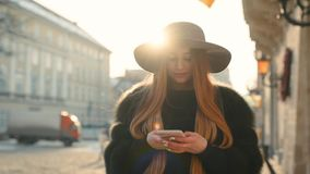 Gorgeous young woman in a bright sunlight uses her phone while standing in the city center. Gladly texts back, looks around. Urban buildings, passersby on the stock video footage