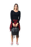 Gorgeous young woman carrying black bag in both hands looking up. Full body length isolated over white studio background royalty free stock photo