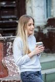 Gorgeous young woman with cup of coffee in city street. Coffee break. Coffee to go. Stylish hipster girl drinking coffee in street. Outdoors fashion portrait stock image