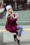 Gorgeous young woman with cup of coffee in city street. Coffee break. Coffee to go. Stylish hipster girl drinking coffee in street. Outdoors fashion portrait royalty free stock photo
