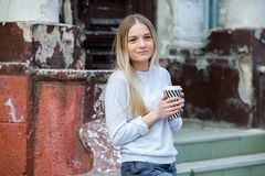 Gorgeous young woman with cup of coffee in city street. Coffee break. Coffee to go. Stylish hipster girl drinking coffee in street. Outdoors fashion portrait stock photos
