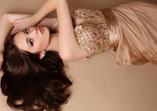 Gorgeous young woman with dark hair and evening makeup, wears luxurious dress. Fashion studio photo of gorgeous young woman with dark hair and evening makeup stock photo