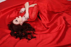 Gorgeous young woman with dark hair and evening makeup, wears luxurious dress stock photo